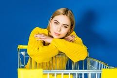 Elegante blondevrouw in geel kledingstuk die op boodschappenwagentje leunen stock foto