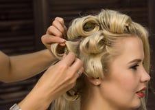 Elegante blondevrouw in schoonheidszaal De kapper doet kapsel in de vorm van grote krul Het kapsel van het conceptenhuwelijk stock afbeelding