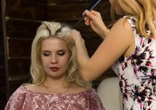 Elegante blondevrouw in schoonheidszaal De kapper doet kapsel in de vorm van grote krul Het kapsel van het conceptenhuwelijk royalty-vrije stock foto