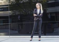 Elegante Blondine in der Klage, die in der überzeugten Haltung steht Stockfotografie