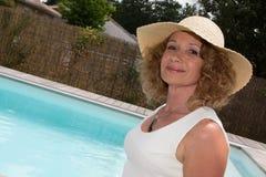 Elegante Blondine mit Hut und Weiß kleidet zum Pool an Stockbild