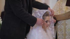 Elegante Braut in einer alten Kirche Ein Mann tr?gt einen Schal auf seinem Kopf zu seiner Frau stock video footage