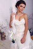 Elegante Braut im Hochzeitskleid, das auf Schwingen am Studio sitzt Stockbild