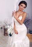 Elegante Braut im Hochzeitskleid, das auf Schwingen am Studio sitzt Lizenzfreie Stockfotos