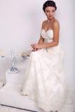 Elegante Braut im Hochzeitskleid, das in verziertem Studio aufwirft Lizenzfreie Stockfotografie