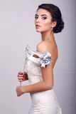 Elegante Braut im Hochzeitskleid mit Maske in ihren Händen Stockfotos