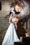 Elegante Braut mit Hochzeitsblumenstrauß über Backsteinmauer Lizenzfreie Stockfotografie