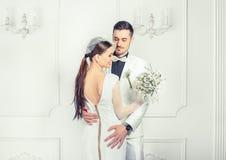 Elegante Braut und Bräutigam, die sinnlich umfasst stockbild