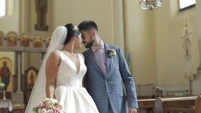 Elegante Braut und Bräutigam, die zusammen in eine alte Kirche geht Gleichheit, Krawatte und Kristallschmucksachen stock video