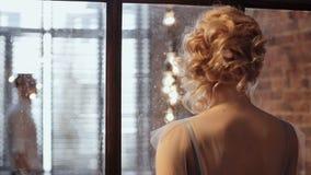 Elegante bruid die dichtbij venster op bruidegom wachten stock footage