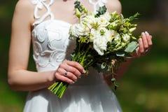 Elegante bruid in een witte huwelijkskleding met kantholding ter beschikking Stock Foto's