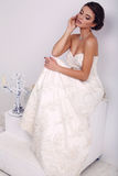 Elegante bruid in huwelijkskleding het stellen in verfraaide studio Stock Foto