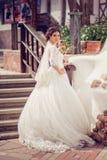 Elegante bruid in huwelijkskleding met ondergedompelde boord in volledige lengte op een achtergrond van een bos of een Park stock fotografie