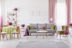 Elegante dagelijkse ruimte met rondetafel met houten stoelen en grijze bank met olijf groene hoofdkussens, modieuze leunstoel naa stock foto