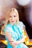 Elegante Dame, die das blaue Kleid sitzt im Dachbodenstudio mit Stern hinter dem Schauen zur Kamera trägt Schönheit, Art und Weis Lizenzfreie Stockfotos