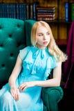Elegante Dame, die das blaue Kleid sitzt im Stuhl in der Bibliothek trägt Schönheit, Art und Weise Stockfotografie