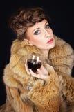 Elegante Dame, die das Rotweinglas trägt braunen Pelzmantel hält Stockbild
