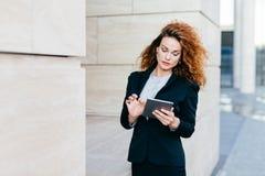 Elegante Dame mit dem gelockten Haar, tragendem schwarzem Anzug, Schreibenmitteilungen oder der Herstellung des Geschäftsberichte lizenzfreie stockbilder