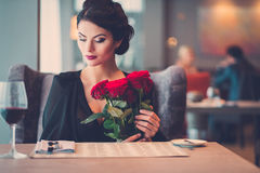 Elegante Dame mit roten Rosen im Restaurant stockfotos