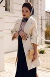 Elegante damenhafte Frau im weißen Mantel mit Zubehör lizenzfreie stockbilder