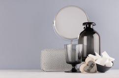 Elegante decortoilettafel in minimalistische stijl - zwarte vaas, glas, kosmetische toebehoren, spiegel, houten hart op grijze mu stock foto's