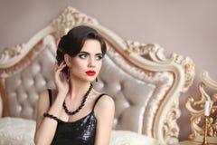Elegante donkerbruine sexy vrouw in modieuze zwarte kleding fashiona Stock Afbeelding