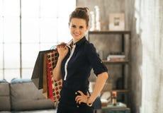 Elegante donkerbruine vrouwenholding het winkelen zakken in zolderwoonkamer Royalty-vrije Stock Foto