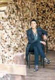 Elegante donkerbruine vrouwenzitting op de stoel Stock Afbeelding