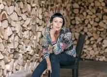 Elegante donkerbruine vrouwenzitting op de stoel Stock Afbeeldingen
