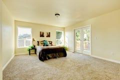 Elegante en eenvoudige slaapkamer in melkachtige tonen met beige tapijt stock foto's