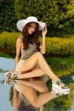 Elegante, erstaunliche und stilvolle junge Dame wirft im Naturpark, im grünen Rasen, im Gras und im Laub am Hintergrund auf stockfoto