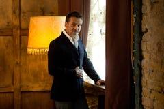 Elegante europäische Mannstellung nahe dem Fenster und Berühren seiner Jacke lizenzfreie stockfotografie
