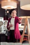 Elegante Frans-Stijl die vrolijke dame verouderen die zich in verlichtingstoonzaal bevinden royalty-vrije stock afbeelding