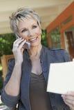 Elegante Frau beim Anruf mit Broschüre in der Hand Lizenzfreie Stockfotos