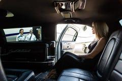 Elegante Frau in der Limousine am Flughafenabfertigungsgebäude Stockfotografie