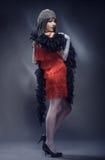 Elegante Frau in der roten Kleider- und Federboa Lizenzfreie Stockfotografie