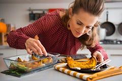 Elegante Frau, die über Teller sich lehnt, wie sie Kürbis dient Lizenzfreies Stockbild