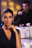 Elegante Frau, die am Abendtische sitzt Stockfotografie