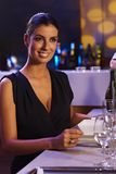 Elegante Frau, die am Abendtische sitzt Stockbild