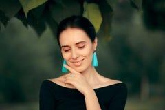 Elegante Frau, die blaues Quasten-Ohrring-Mode-Porträt trägt stockfotos
