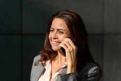 Elegante Frau, die draußen am Telefon spricht Stockbilder