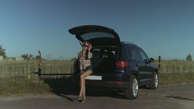 Elegante Frau, die nahe Auto in der Landschaft aufwirft stock video