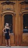 Elegante Frau, die nahe Weinleseholztüren steht Stockbild