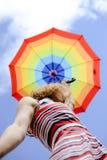 Elegante Frau, die Regenbogenregenschirm über sonnigem hält Stockfotografie