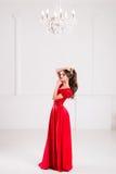 Elegante Frau in einem langen roten Kleid steht in einem hellen Raum w Lizenzfreies Stockbild