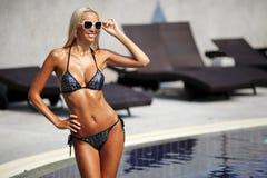 Elegante Frau im Bikini mit dem gebräunten dünnen Körper, der nahe einem Schwimmen aufwirft Lizenzfreies Stockfoto