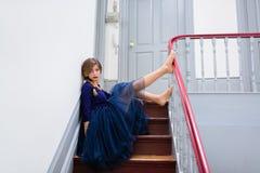 Elegante Frau im blauen Kleid wirft auf der Treppe auf Stockfotos