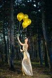 Elegante Frau im langen Kleid mit Ballonen im Holz lizenzfreie stockfotografie