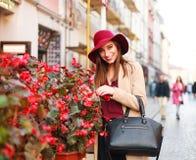 Elegante Frau im Mantel und im purpurroten Hut auf touristischer Stadt der Straße mit lizenzfreies stockfoto