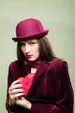 Elegante Frau im roten Hut, der Herz hält, formte Lizenzfreie Stockfotografie